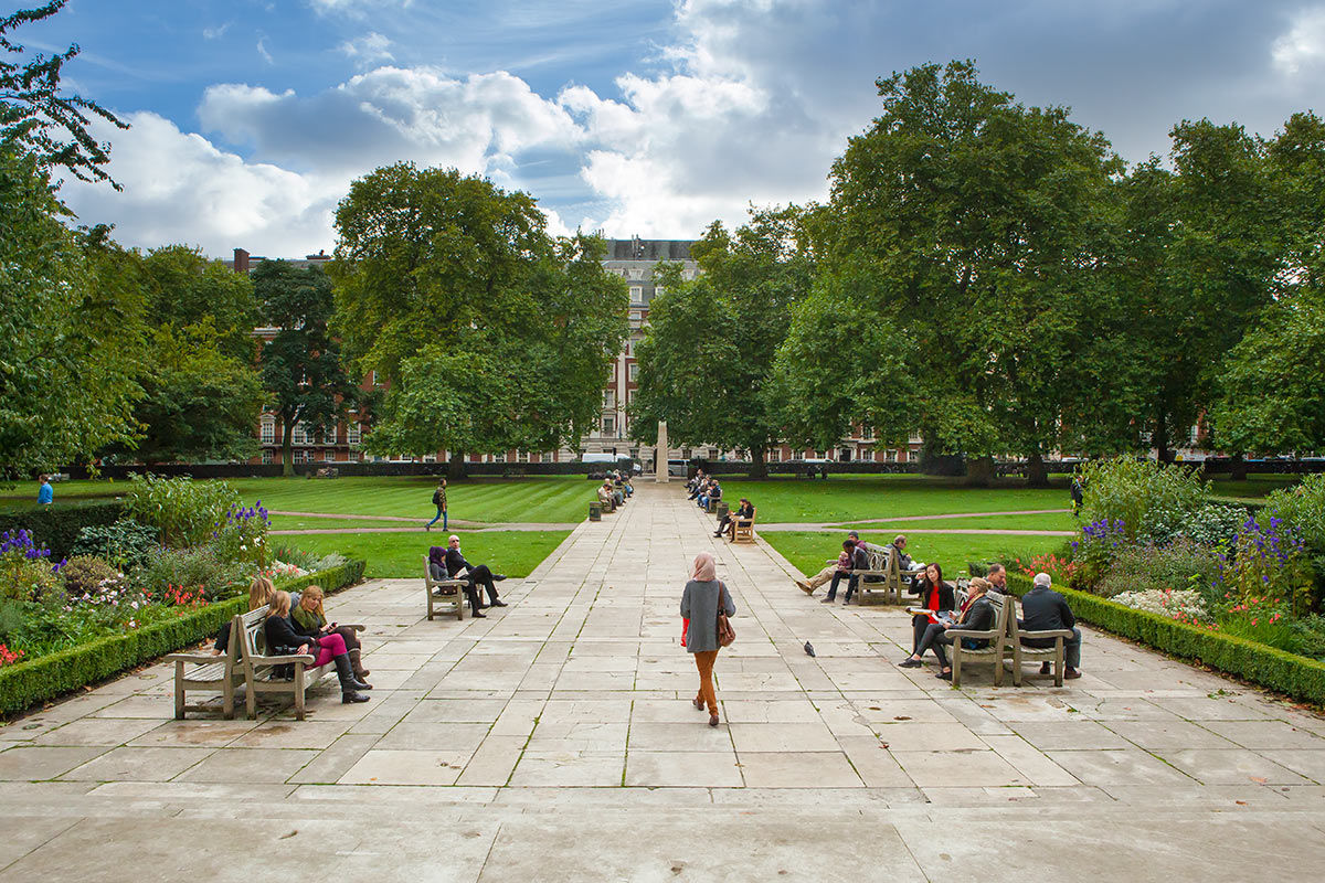 A daytime view of Grosvenor Square showing green grass, trees and flowers in bloom, London, United Kingdom.