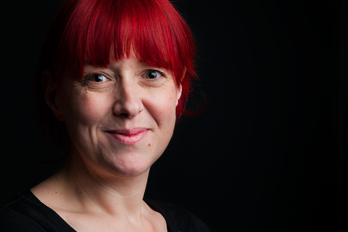Portrait of a lady with bright red hair against a dark background, London, United Kingdom.